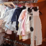 Young beautiful woman shopping, standing in department store in front of rack with baby clothes, looking for new outfit for toddler kid, close-up of hands